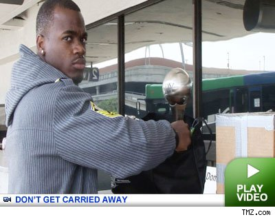 adrian peterson with his espy at the airport on tmz